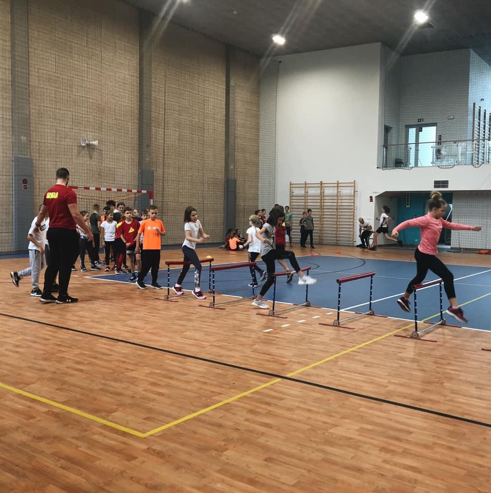 Dzieci z grupy podstawowej ćwiczące na sali gimnastycznej